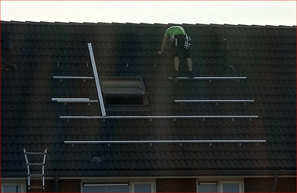 man op dak zonnepanelen